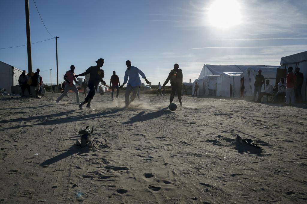 Flera personer spelar en match i fotboll innan de ska gŒå de 2,5 timmarna till vŠägen utanföšr tunneln.