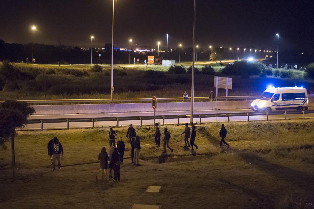 Fransk kravallpolis jagar bort migranterna som fšörsöšker ta sig upp påŒ lastbilar som Œska åka genom tunneln mot England.