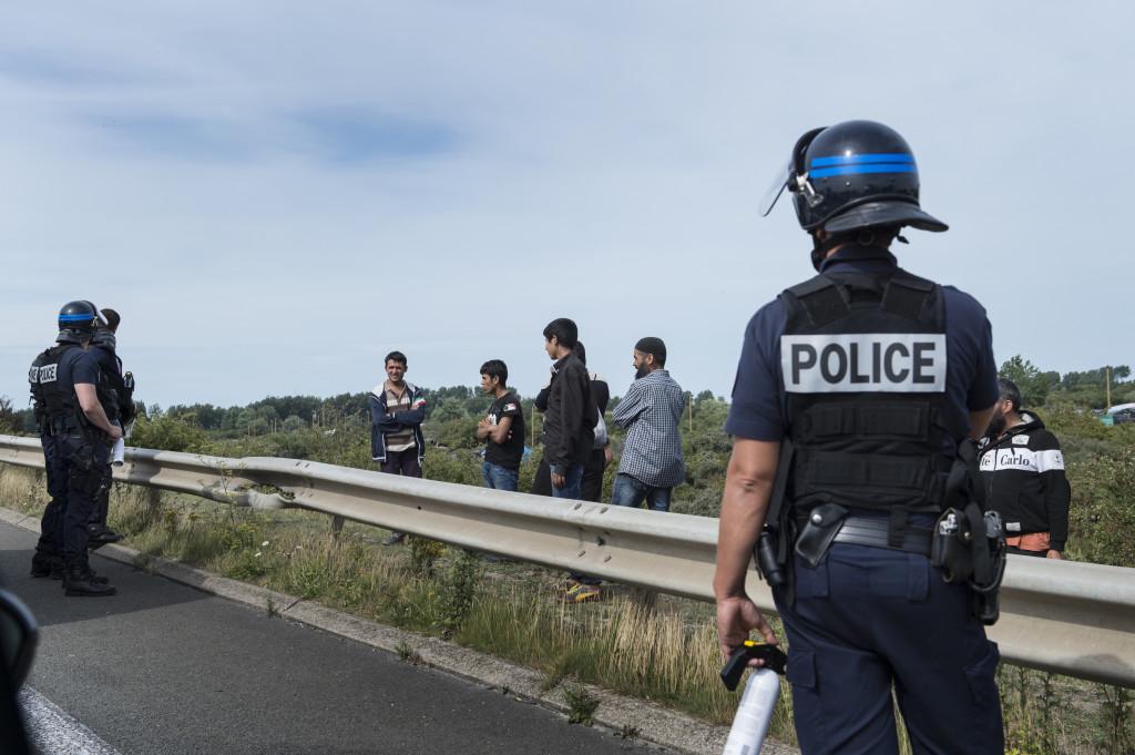 Den franska kravallpolisen vaktar vŠägen som gåŒr utanföšr flyktinglŠägret i Calais.
