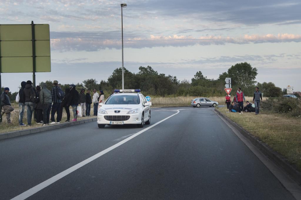 Fransk polis jagar bort migranterna som föšrsöšker ta sig upp påŒ lastbilar som Œåker genom tunneln i Calais mot England.